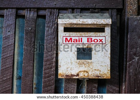 Mailbox hanging on wooden fence, Old white mailbox