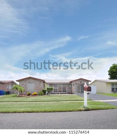 Mailbox on Suburban Neighborhood Street Residential Ranch Style Home Sunny Blue Sky Day - stock photo