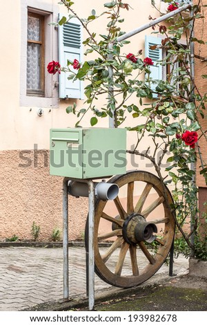 Mailbox with wheel and flowers in Mittelbergheim, Alsace, France
