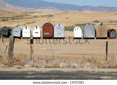 Mailboxes on a dusty road - stock photo