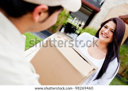 Mailman delivering a parcel at a womans house - stock photo