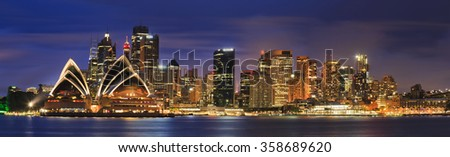 Main australian city Sydney at sunset across Harbour brightly illuminated. Cityscape landmarks including high-rise office towers and buildings around circular quay - stock photo