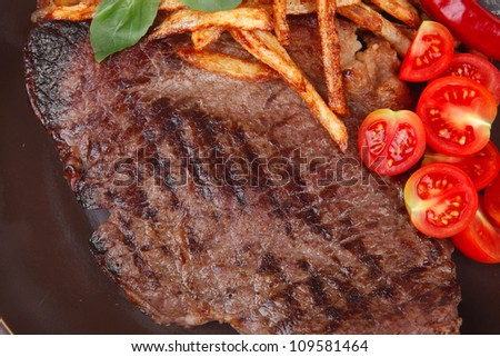 main course : grill beef steak with potato chips and fresh cherry tomato , red hot chili peppers on plate isolated on white background - stock photo