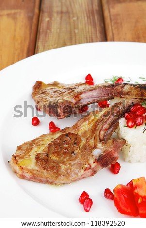 main course: grilled ribs with rice and tomatoes on white dish over wood