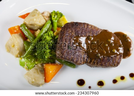Main dish of grilled stake with black pepper sauce, garnished with green bean and carrot served in a white plate - stock photo