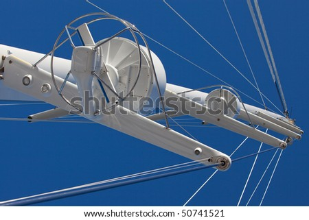 Main mast from a luxury yacht against the blue sky. The mast features two radars and rigging - stock photo