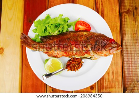 main portion of two grilled fish served on plate with tomatoes and spices - stock photo