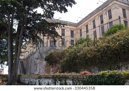 main prison building and garden wall on alcatraz island in san francisco bay of california - stock photo