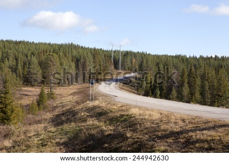 Main road through Nordic rural countryside. Lay-by and an electrical line cross the highway. - stock photo