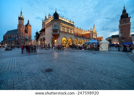 Main Square in the Old Town of Krakow in Poland at dusk. On the left St Mary Basilica, in the middle Cloth Hall (Sukiennice), on the right Town Hall tower. - stock photo