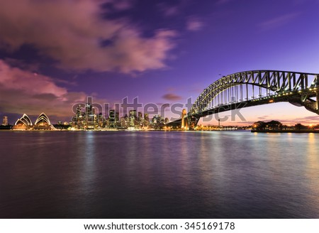 main Sydney landmarks at sunset across harbour with blurred clouds and water reflecting bright lights of colourful illumination from houses to Bridge Arch