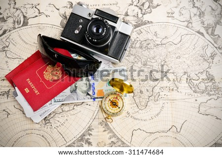 Main travel items for journey over mediaval world map - stock photo