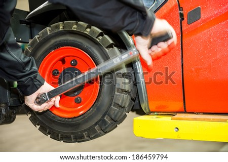 Maintenace on a forklift, a worker is changing the tyres. - stock photo