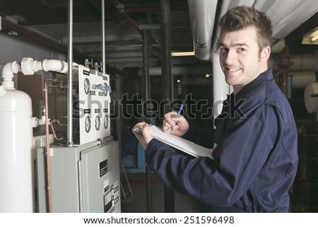 maintenance engineer checking technical data of heating system equipment in a boiler room - stock photo