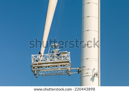Maintenance of a wind turbine against a clear blue sky - stock photo
