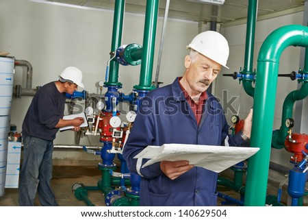 maintenance repairman engineer of heating system equipment in a boiler house - stock photo