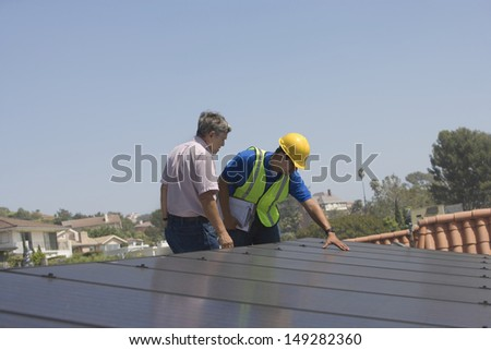 Maintenance workers inspecting solar panels on rooftop - stock photo