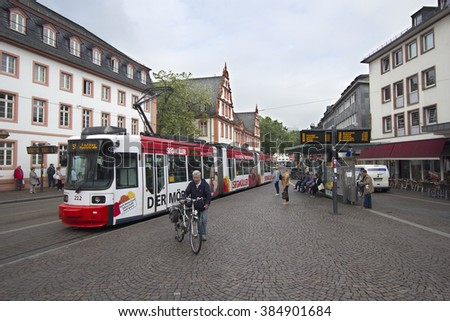 Mainz, Germany - April 29, 2014: People waiting at a tramstop with a tram just departing in central Mainz, Germany on April 29, 2014