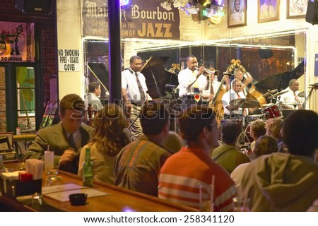 Maison Bourbon Jazz Club with Dixieland band and trumpet player performing at night behind bar with drinking customers in French Quarter in New Orleans, Louisiana - stock photo