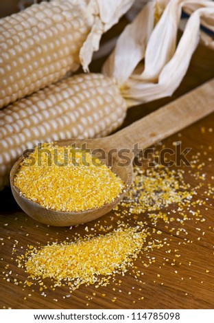 maize flour over spoon on a wooden table - stock photo