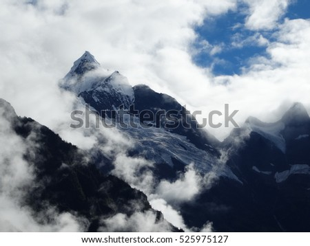 Majestic and pure Meili Snow mountain Peak in Yubeng Village in Yunnan Province, China, with clouds and sunshine beams, blue and white