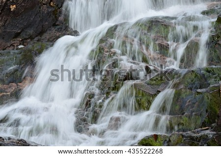majestic and serene waterfall on the top of the kaperdalen mountain in northern norway in summer - stock photo