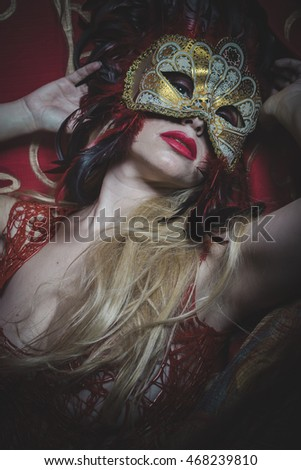 Majestic Blonde with gold mask on red cloth embroidered golden thread, mystery and sensuality