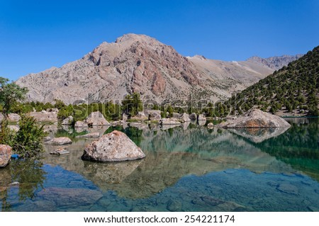 Majestic blue mountain lake with large stone in Tajikistan - stock photo