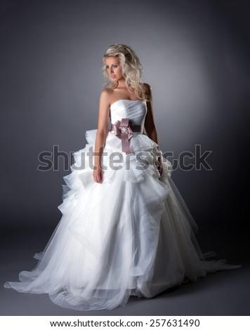 Majestic bride posing in lush wedding dress - stock photo