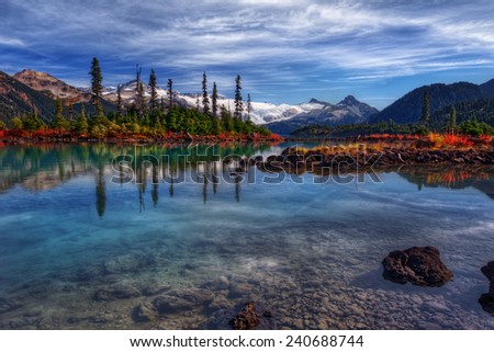 Majestic evergreen trees towering over crisp clear lake - stock photo