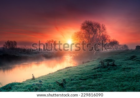 Majestic foggy river with fresh green grass in the sunlight. Dramatic colorful scenery. Dnister river, Ternopil. Ukraine, Europe. Beauty world. Retro style filter. Instagram toning effect. - stock photo