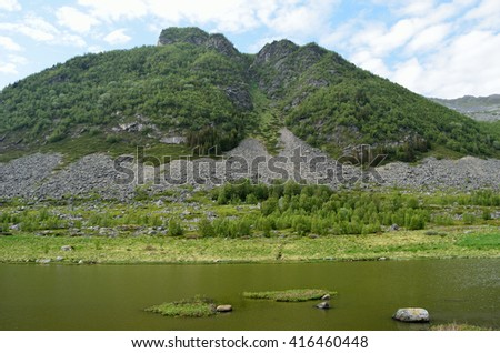 majestic green lush mountain with small lake underneath in summertime - stock photo
