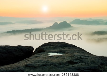 Majestic mountain cut the lighting mist. Deep valley is full of colorful fog and rocky hills are sticking up to Sun.  - stock photo