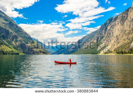 Majestic mountain lake in Canada. Seton Lake in British Columbia, Canada. Red canoe. - stock photo