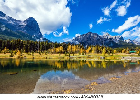 Majestic mountains and scenic cumulus clouds are reflected in the water. Canmore, near Banff National Park. The concept of recreational tourism