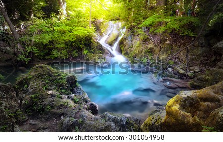 Majestic nature background of mountain river stream and small blue water lake in wild tropical forest - stock photo