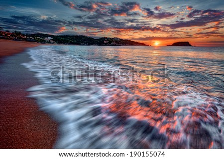 Majestic ocean sunset with a breaking wave 4 - stock photo