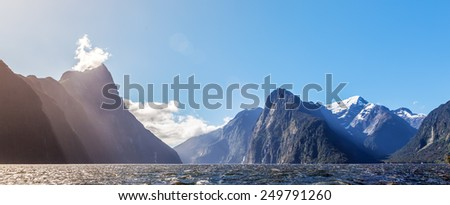 Majestic snow capped peaks of Milford Sound with sun rays. Fiordland, New Zealand - stock photo