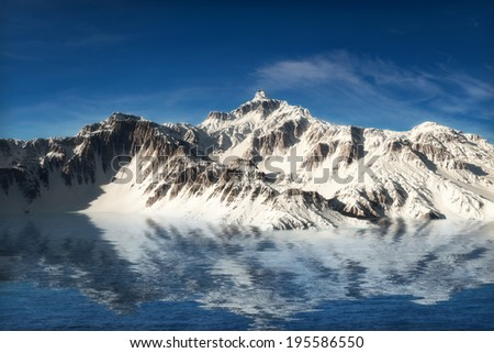 Majestic snow covered mountains reflecting in the water - stock photo