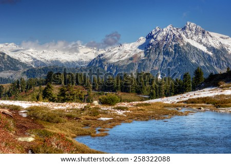 Majestic snow-topped mountains with evergreen trees and a clear lake - stock photo