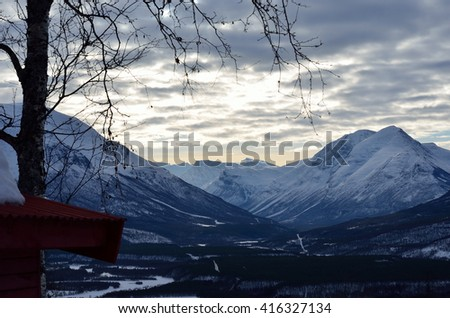 majestic snowy mountain and river landscape lookind down on to the small settlement of Rundhaug, maalselv municipality - stock photo