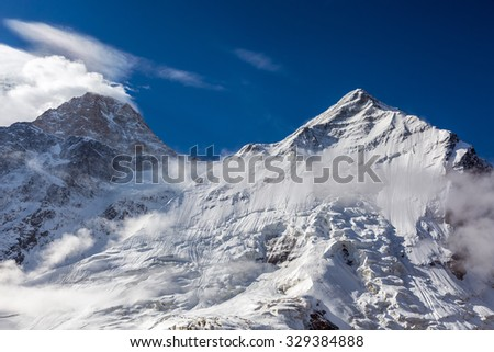 Majestic View of High Altitude Snowbound Mountain Peaks with Glaciers Rocks Snow Clouds and Blue Sky Daylight  - stock photo
