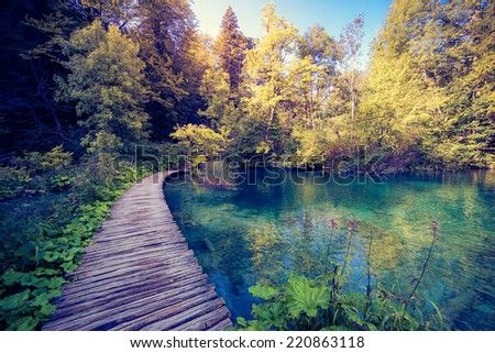 Majestic view on lake with turquoise water and sunny beams in Plitvice Lakes National Park. Forest glowing by sunlight. Croatia. Europe. Dramatic morning scene. Beauty world. Instagram effect. - stock photo