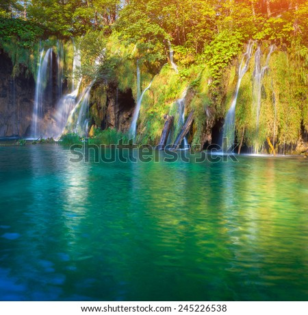 Majestic view on waterfall with turquoise water and sunny beams in the Plitvice Lakes National Park. Forest glowing by sunlight. Croatia. Europe. - stock photo