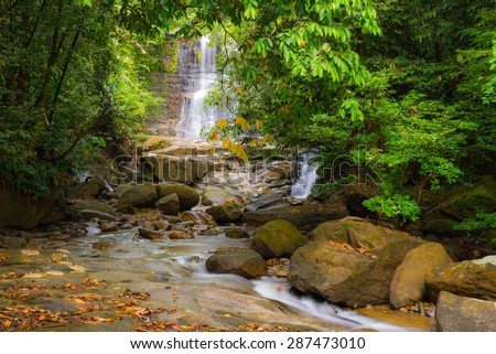 Majestic waterfall amid the dense lush green jungle of Kubah National Park, West Sarawak, Malaysian Borneo, with flowing stream and boulders in the foreground. Blurred effect on water, long exposure. - stock photo