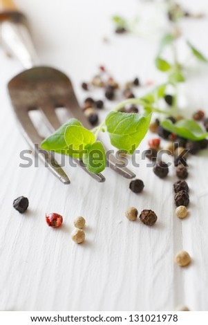 Majoram and a fork, assorted peppercorns on a white wooden table useful as a herb concept background - stock photo