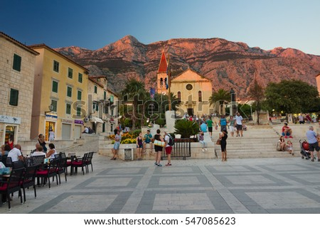 Makarska, Croatia - August 16, 2016: Tourists on square in front of St. Mark´s Cathedral of Makarska with Biokovo Mountain at sunset, Croatia