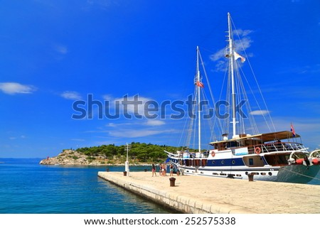Makarska harbor with traditional sail boat and tourists on a pier, Croatia - stock photo