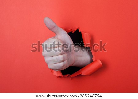 Make a thumb up sign by use his hands through hole on the red paper. - stock photo