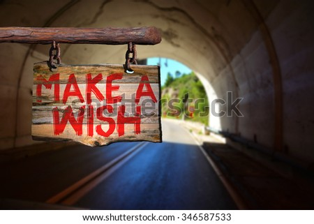 Make a wish motivational phrase sign on old wood with blurred background